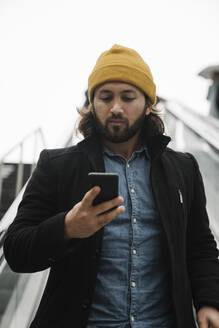 Portrait of man wearing yellow cap standing on escalator looking at smartphone - AHSF01149