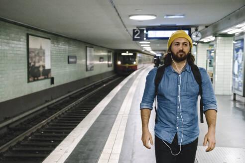 Portrait of man with backpack and earphones walking at platform, Berlin, Germany - AHSF01170