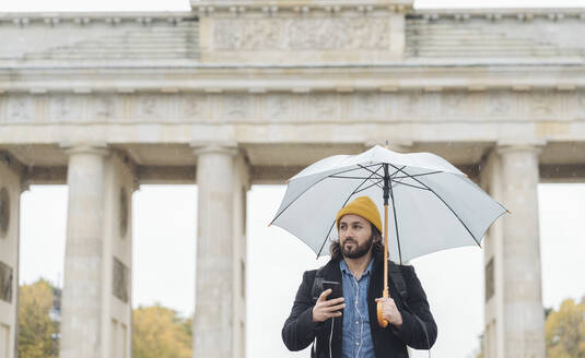 Man with umbrella using smartphone in front of Branderburg Gate, Berlin, Germany - AHSF01176