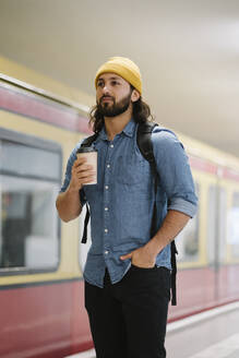 Portrait of man with backpack and coffee to go waiting at platform, Berlin, Germany - AHSF01182