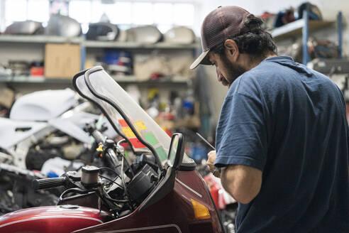 Mechanic in a repair garage repairing a motorcycle - MTBF00172