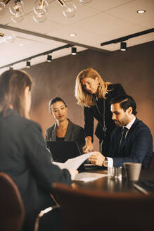 Mature female lawyer planning with coworkers in meeting at law office - MASF14465