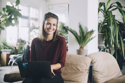 Portrait of smiling creative businesswoman with laptop in office - MASF14675