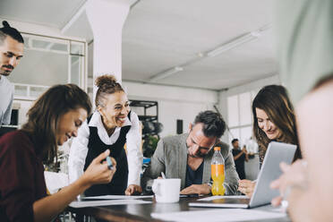 Smiling creative business people working at table in office - MASF14741
