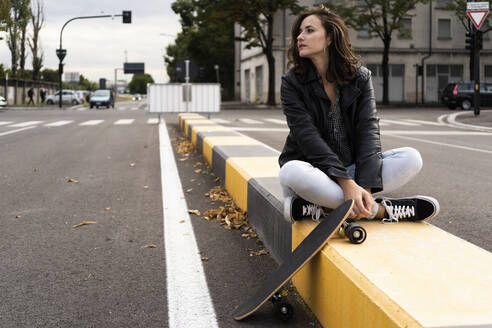 Young woman with skateboard sitting on bollard looking at distance - GIOF07682