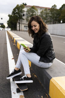 Smiling young woman with skateboard sitting on bollard using smartphone - GIOF07688