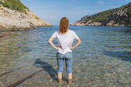 Young woman standing in water at the beach - AFVF04195