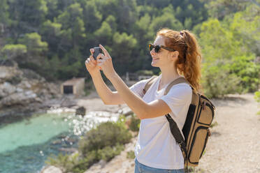 Redheaded woman standing on viewpoint and photographing with her smartphone - AFVF04198