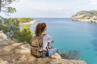 Redheaded woman sitting on viewpoint and looking at distance, Ibiza - AFVF04201