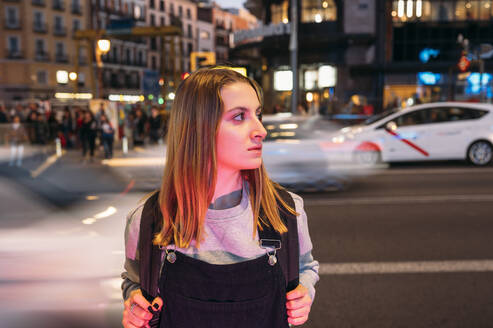 Young woman standing at night in the city on the street - JCMF00284
