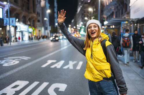 Young woman in the city hailing a taxi at night - JCMF00290