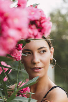 Portrait of young woman in a park with pink blossoming flowers - AFVF04205