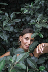 Portrait of young woman among green leaves - AFVF04208