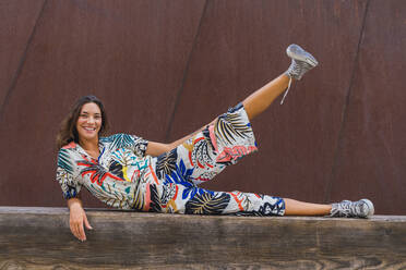Portrait of smiling young woman lying on wooden bench lifting leg - AFVF04217