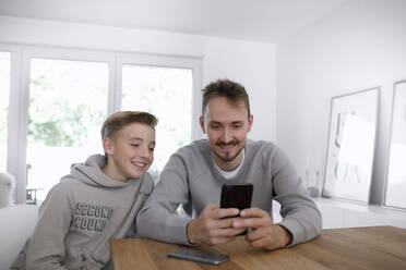 Young man and teenager using smartphone in a living room - KMKF01138