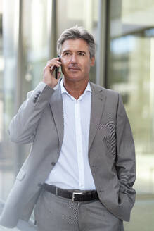 Mature businessman on the phone in the city - DIGF08873