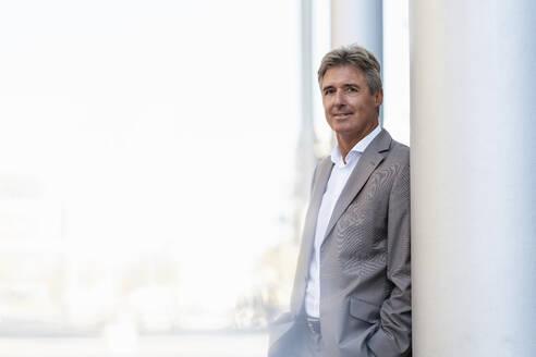 Portrait of confident mature businessman leaning against a column - DIGF08879