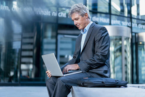 Mature businessman using laptop in the city - DIGF08888