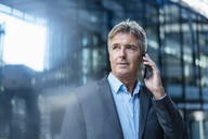Mature businessman on the phone in the city - DIGF08897