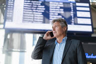 Mature businessman on the phone at the station - DIGF08903