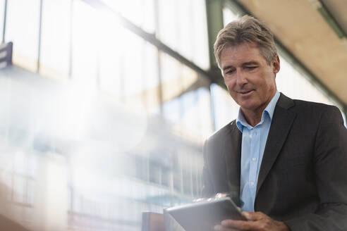 Mature businessman using tablet at station platform - DIGF08918
