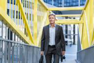 Mature businessman walking on a bridge - DIGF08924