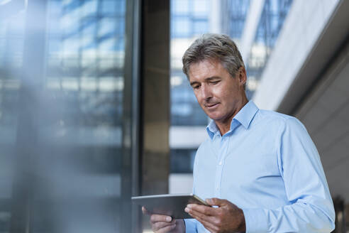 Mature businessman using tablet in the city - DIGF08930