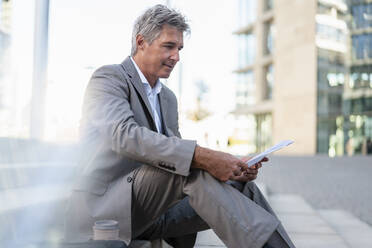 Mature businessman reviewing documents in the city - DIGF08933