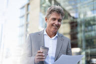 Smiling mature businessman with takeaway coffee reviewing documents in the city - DIGF08936