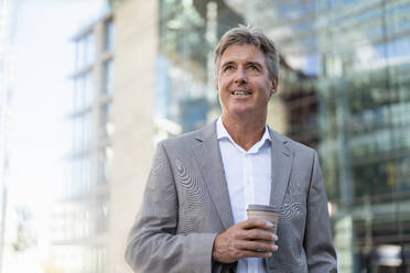 Mature businessman holding reusable takeaway coffee cup in the city - DIGF08939