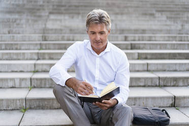Mature businessman sitting on stairs looking at notebook - DIGF08948
