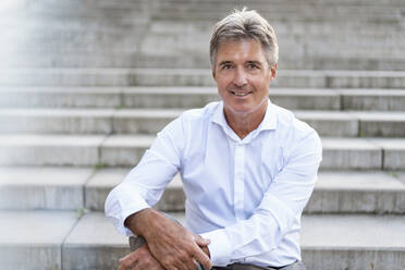 Portrait of confident mature businessman sitting on stairs - DIGF08954