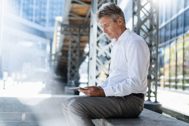Mature businessman using tablet in the city - DIGF08960