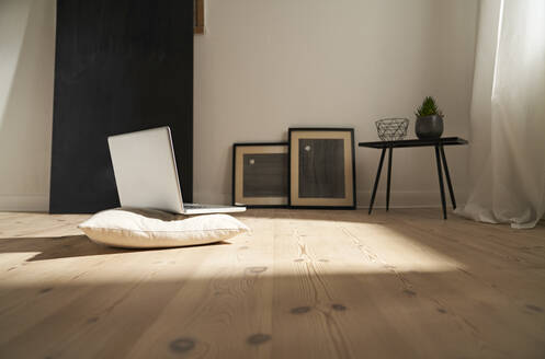 Laptop on cushion and wooden floor in a modern room - PDF01889