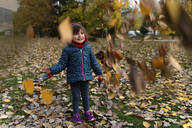 Little girl playing with autumn leaves outdoors - GEMF03299