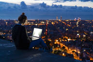 Young woman using laptop at dawn above the city, Barcelona, Spain - GIOF07691
