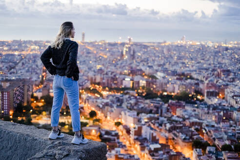 Rear view of young woman standing above the city at dawn, Barcelona, Spain - GIOF07694