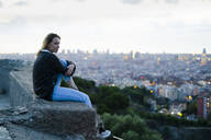 Young woman sitting above the city at sunrise, Barcelona, Spain - GIOF07697