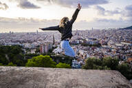 Carefree young woman jumping above the city at sunrise, Barcelona, Spain - GIOF07703