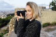 Young woman taking pictures above the city at sunrise, Barcelona, Spain - GIOF07706