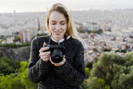 Young woman with camera above the city at sunrise, Barcelona, Spain - GIOF07709