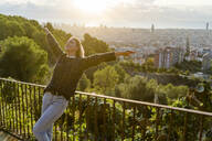 Carefree young woman standing above the city at sunrise, Barcelona, Spain - GIOF07712