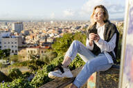 Young woman sitting on railing above the city holding cell phone, Barcelona, Spain - GIOF07718
