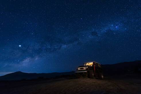 Indonesia, East Java, Milky Way galaxy on blue starry night sky over car parked in Bromo Tengger Semeru National Park - TOVF00131