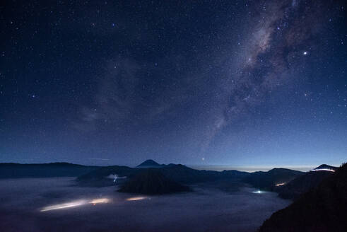 Indonesia, East Java, Scenic view of Milky Way galaxy on starry night sky over Mount Bromo shrouded in fog - TOVF00134