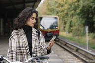 Woman with bicycle and cell phone on an underground station platform, Berlin, Germany - AHSF01197