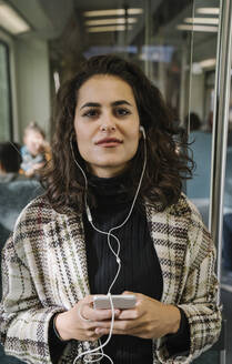 Portrait of beautiful young woman with earphones and smartphone on a subway - AHSF01218