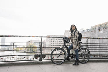 Woman with a bicycle standing on a bridge in the city, Berlin, Germany - AHSF01227