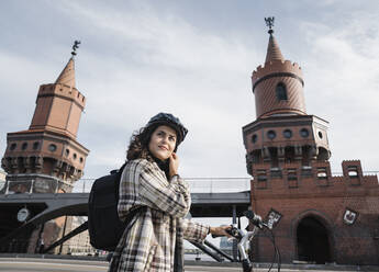 Woman with a bicycle in the city at Oberbaum Bridge, Berlin, Germany - AHSF01230