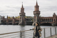 Smiling woman with bicycle and smartphone in the city at Oberbaum Bridge, Berlin, Germany - AHSF01233